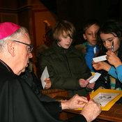 Bischof Norbert Trelle gibt Autogramme auf den Mappen der Kommunionkinder in St. Heinrich.