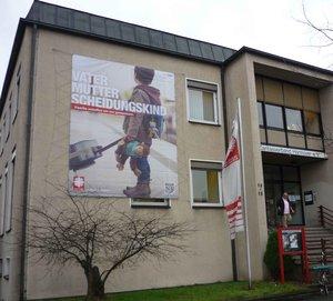 An der Fassade des Caritasverbandes am Leibnizufer wirbt ein neues Blow-Up für die Jahreskampagne.