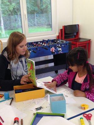 """Eine Betreuerin und ein Flüchtlingskind beim gemeinsamen Spiel: In lockerer Atmosphäre gelingt es """"Wortfinder"""", den Kindern beim Erlernen der Sprache zu helfen und sie vor allen Dingen auch emotionale zu stabilisieren. © Caritas"""